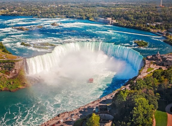 Aerial top landscape view of Niagara Falls and tour boat in water between US and Canada.  Horseshoe of famous Canadian waterfall on sunny day