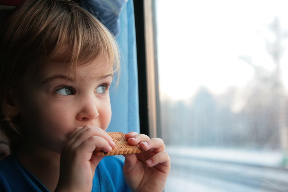 Little girl eating a snack on the train